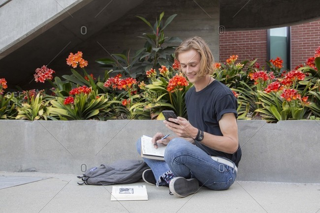 Male student sitting by flowers with books, smiling at text message
