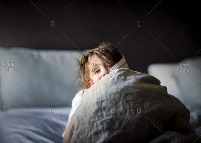 A Small Young Boy Playing Peek-A-Boo In A Bed With Blankets