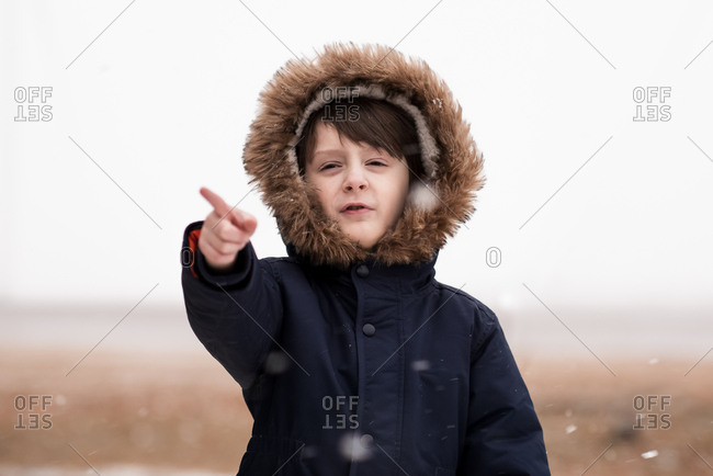 A Small Young Boy Pointing At Falling Snow
