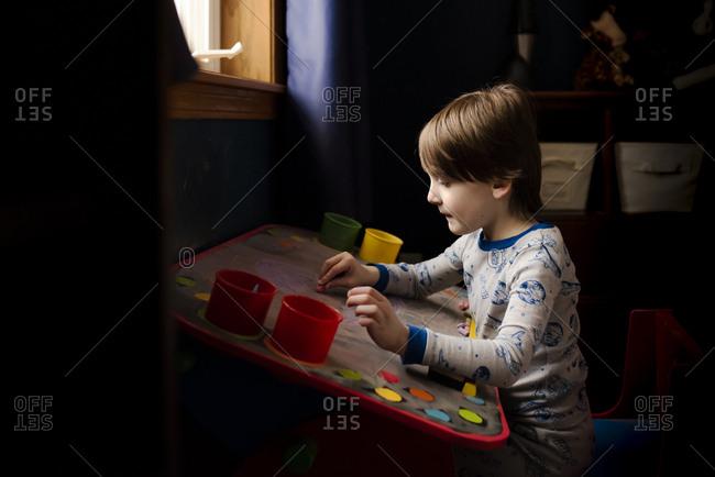 A Small Boy Making Artwork On A Chalk Board