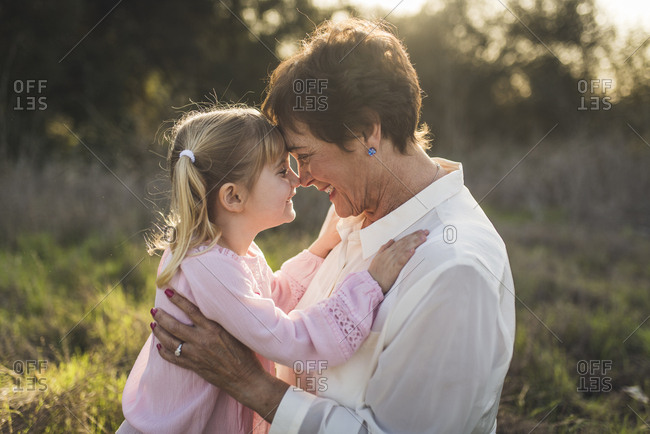 Portrait of grandmother and granddaughter embracing and smiling