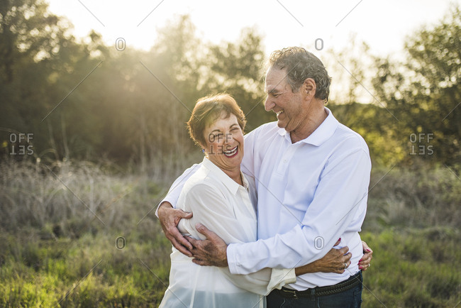 Senior couple hugging and laughing outside in backlight