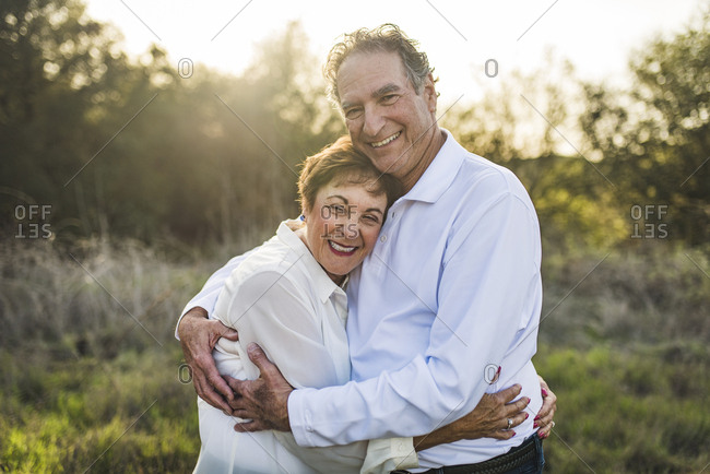 Senior couple hugging and smiling outside in backlight