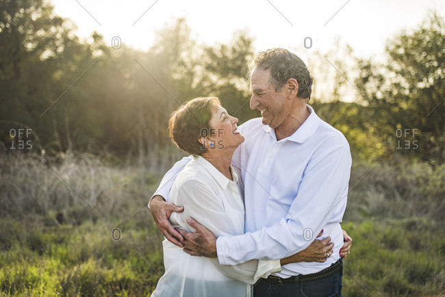 Senior couple hugging and looking at each other outside in backlight