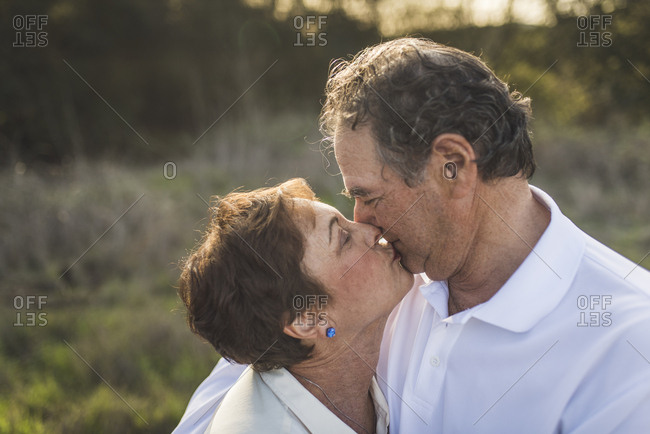 Close up of senior couple kissing each other outside in backlight