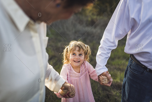 Little girl holding hands with grandparents, looking up and smiling