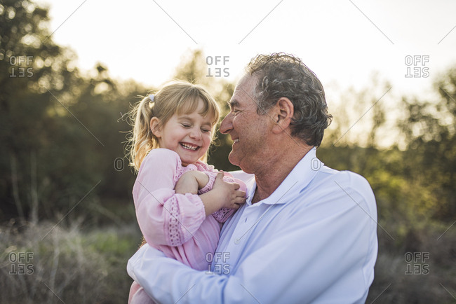 Grandpa holding granddaughter in field and laughing