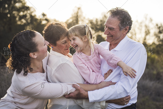 Multigenerational family embracing and laughing in field
