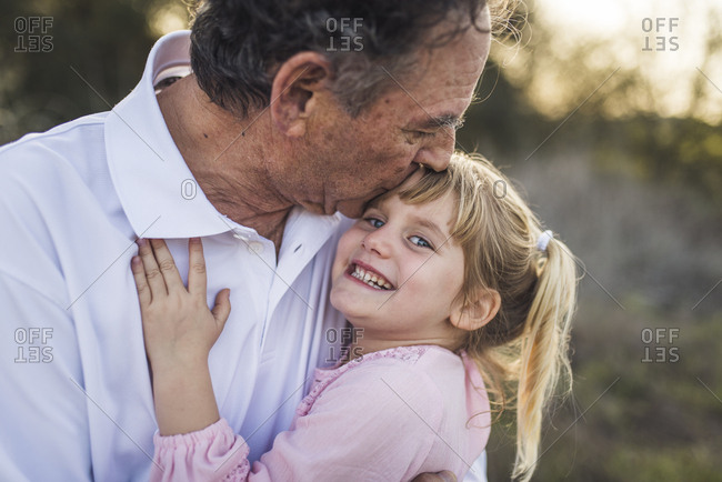Grandfather hugging young granddaughter and kissing her forehead