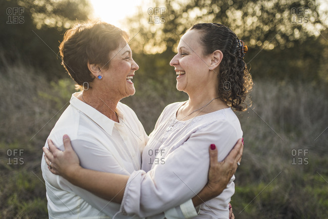 Close up portrait of adult mother and daughter embracing and laughing