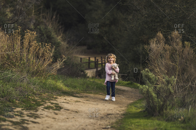 Little girl walking with her stuffed animal and looking ahead