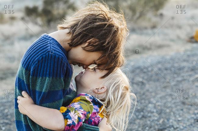 Portrait of adorable siblings hugging at natural park