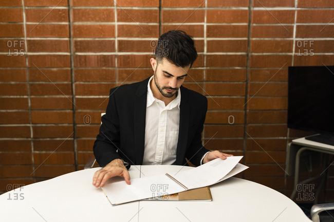 Young businessman looking at catalog