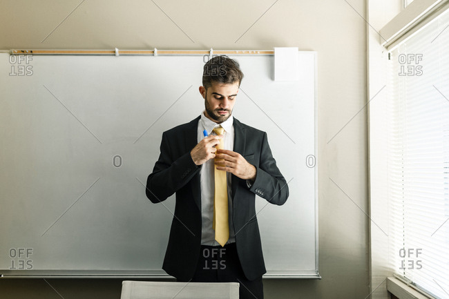 Man fixing tie by white board at office