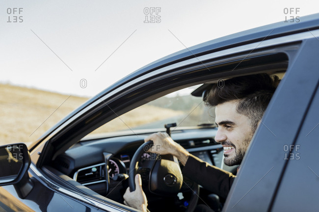 Smiling man in suit driving a car by wheat field at sunset