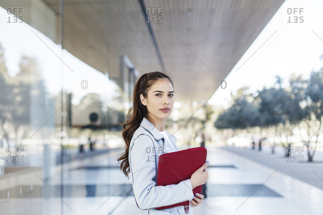 Portrait of young woman holding laptop case by corporate building