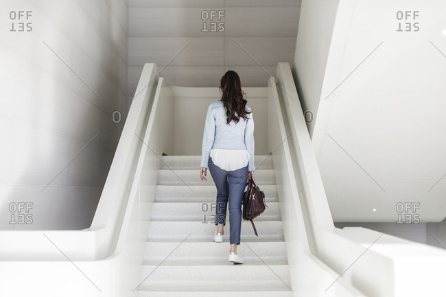 Back view of young lady with message bag by white staircase