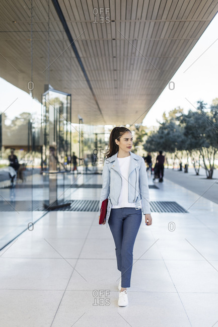 Attractive young woman walking with laptop case by corporate building