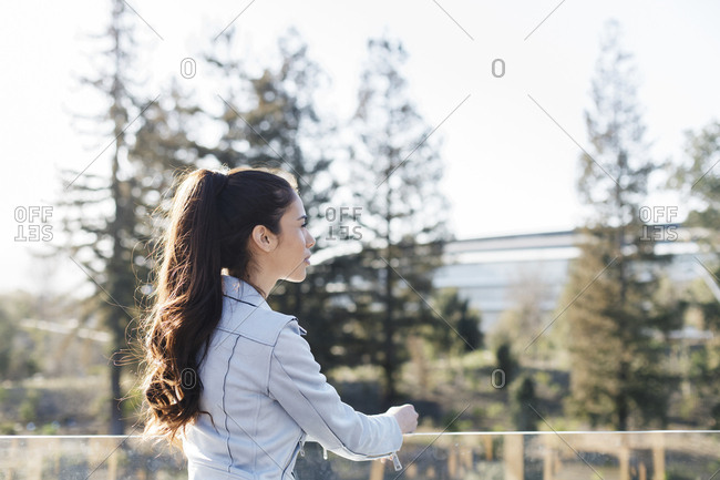Side view of beautiful young woman dreaming by corporate building