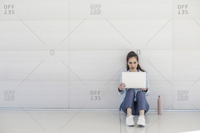 Woman sitting on floor with laptop by white wall