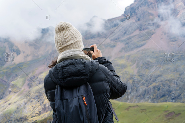 Young Hip Woman Taking a Photo While Exploring The Andes Mountains.