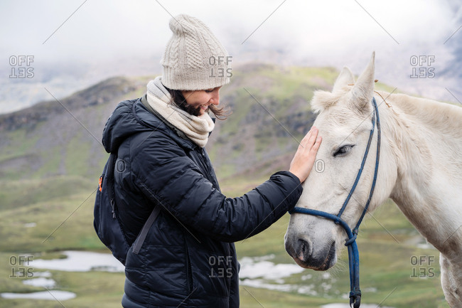 Young Hip Woman Stroking a White Horse. Exploring The Andes Mountains.