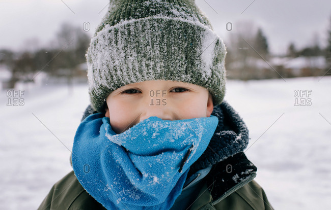 young boy aged 6 standing in the snow with snow on his face and hat