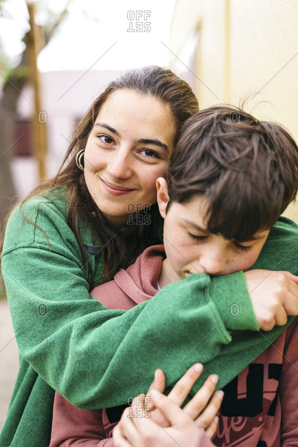 Young couple hugging outdoors while girl looking camera