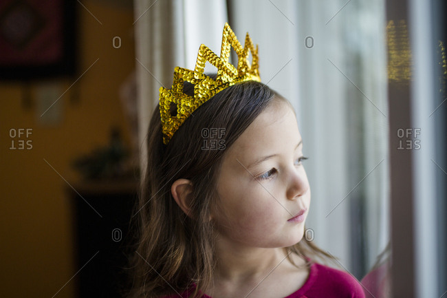 Portrait of serious little girl in a golden crown looking out window
