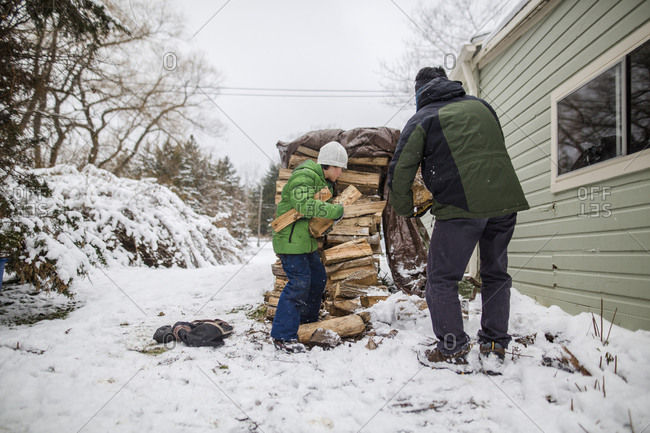 A small boy helps his father gather wood from a wood stack in the snow