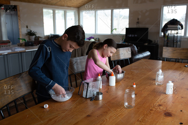 Kids making homemade slime with glue together at table