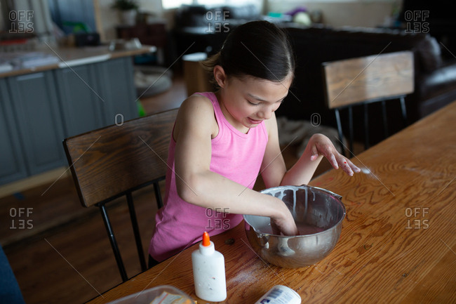 Tween girl making homemade slime with glue