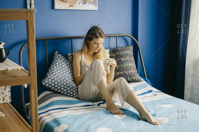 young beautiful woman a freelancer is working from home on the bed