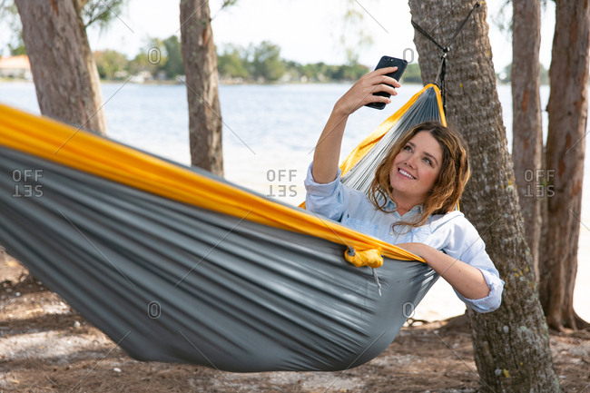 Brunette woman takes selfie with mobile phone relaxing on a hammock.