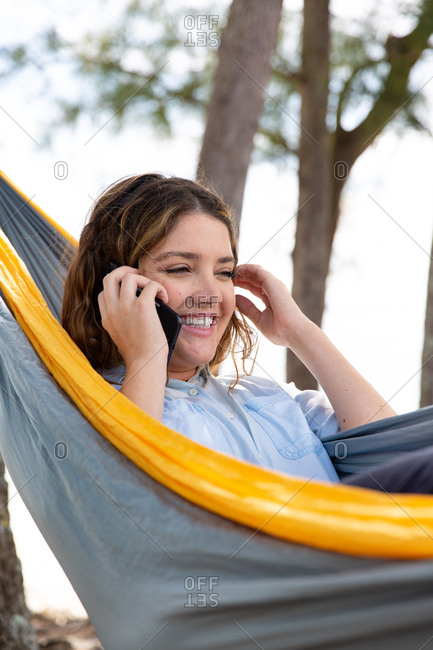 Brunette woman talks on her mobile phone while relaxing on a hammock.