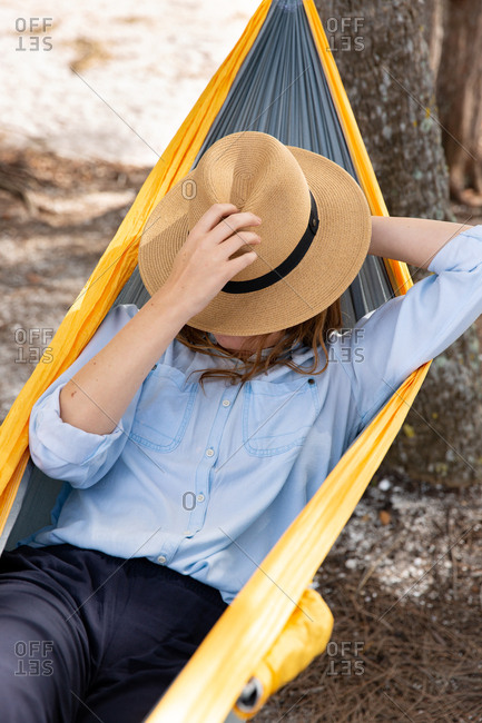 Woman rests on a hammock along the coast with sunhat over her face.