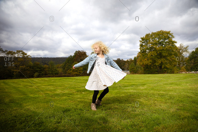little girl with blonde hair spinning in flowy dress on hilltop