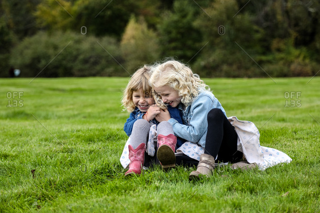 two sisters sitting on grass laughing and hugging together