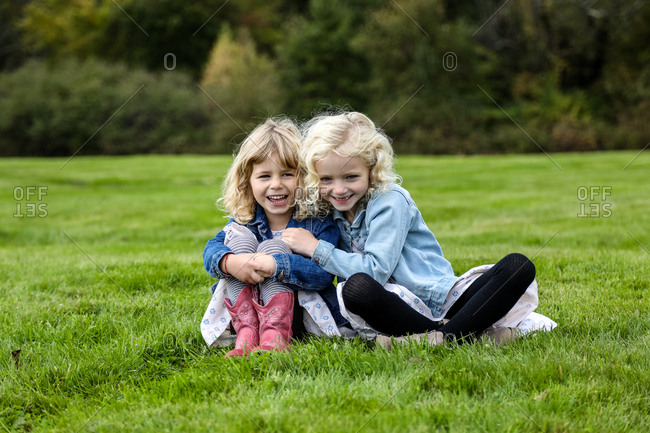 two sisters sitting on grass smiling towards camera linked arms