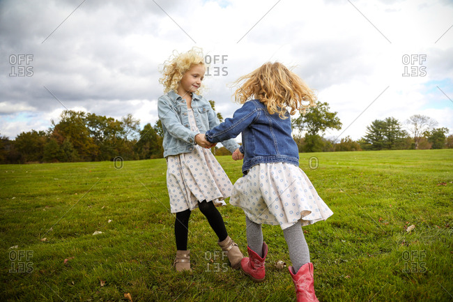 two sisters holding hands spinning together in a field