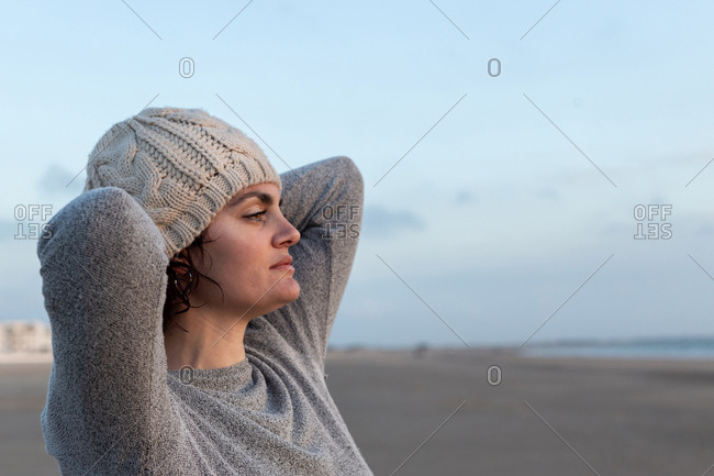 Portrait of a beautiful woman looking at the sunset on the beach