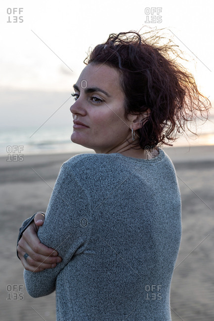 Portrait of a beautiful woman feeling the wind on the beach