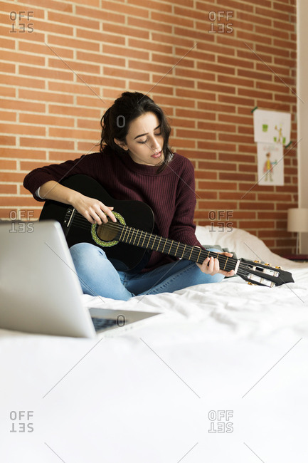 Woman playing acoustic guitar at home