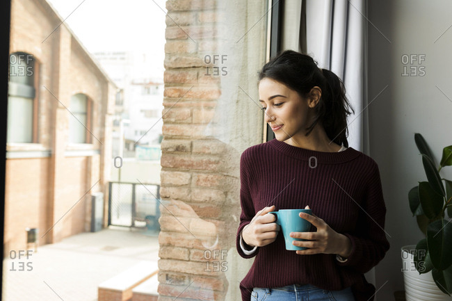 Woman drinking coffee and looking through the window
