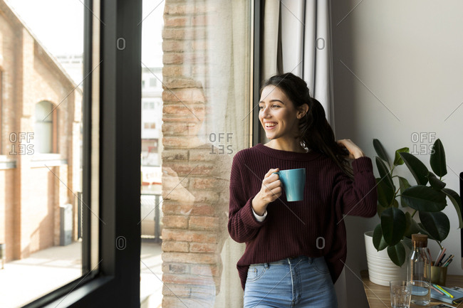 Smiling woman drinking coffee and looking through the window