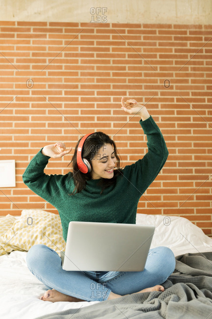 Happy woman listening to music on her laptop in bed