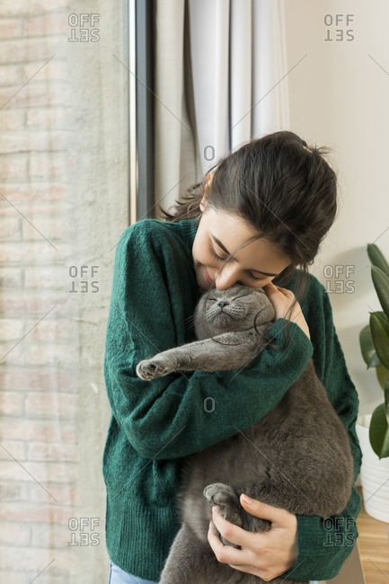 Portrait of a woman snuggling with her kitty by the window