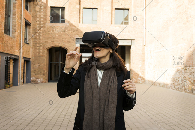 Young woman using a VR headset outdoors