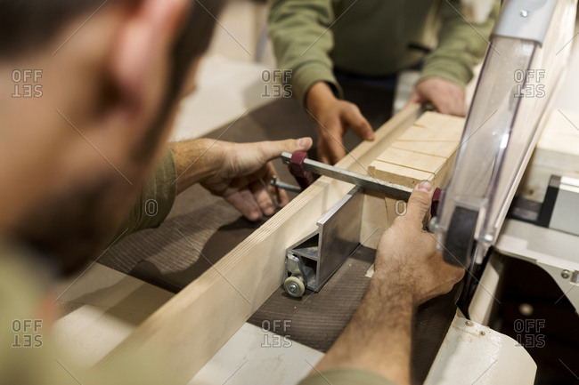 Two carpenters guiding plank through saw