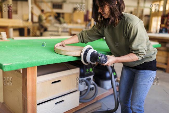 Female carpenter sanding down a wooden piece in woodshop